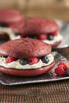 Sweet red velvet cake sandwiches with a fluffy white filling and fresh berries!
