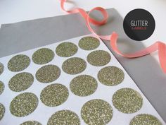 Glitter labels. Spray with adhesive, remove the negative space, spread glitter across.