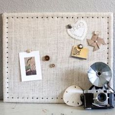 Transform an old boring cork board with burlap and upholstery tacks. Step by step instructions included.