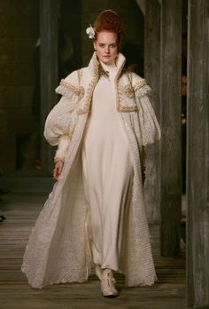 Tudor-inspired outfit from Chanel's pre-Fall 2013. Winter-white coat with an ornately gold beaded heavy fabric bodice, cap over-sleeve, and lower sleeve gauntlets. The rest of the coat, including balloon / poet under-sleeves, is a scalloped-edge lace. Worn over a simple turtleneck sweater dress.