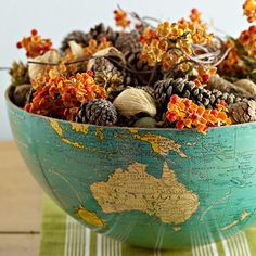 Global Table Setting  Turn an old globe into a distinctive centerpiece. Separate the globe's hemispheres and fill each one with colorful leaves, seedpods, small pumpkins and gourds, pinecones, and other fall items such as bittersweet. This arrangement is as attractive as it is easy. - Dave and Amy should have one of these!