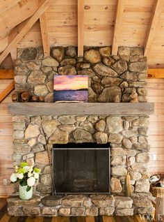 Our Flintstones-style fireplace was made from rocks on the island. The floor is stained in three different colors to reflect the striped granite rock of the area. Next to the painting of the sunset I did one afternoon many summers ago is a jar of snakeskins that my brothers found on the island.