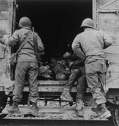 30th April 1945  Liberation of Dachau, US troops opening the door on a freight truck full of dead prisoners.  Lee Miller, 8th. April 1945