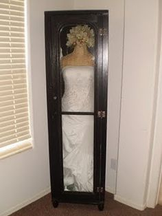 I want something like this to put my dress in so we can display it in our bedroom. Since i'm short though, I want to have shelves either above or below the dress to display our marriage certificate, photo's, maybe even one of the centerpieces for the tables. I also want to have the dress hanging on a simple white hanger, not on a dress form like this one.