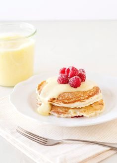 Lemon Raspberry Pancakes recipe - These pancakes are packed full of lemon flavor. Zest and juice in the batter, and lemon curd slathered in between each layer. Blueberries would also be good in this recipe, but I had raspberries that needed to be eaten. And eaten they were. #brunch #lemon #pancake