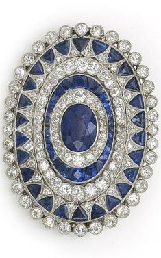 An art deco sapphire and diamond brooch, circa 1925 centering an oval-shaped sapphire framed with several successive rows of old European and single-cut diamonds and calibré and triangular-cut sapphires; central sapphire weighing approximately: 2.50 carats; estimated total diamond weight: 2.60 carats; mounted in platinum.