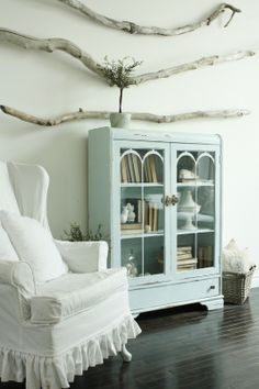 antique blue cabinet, with driftwood on the walls. Love the dark wood floors and that white slipcovered chair!