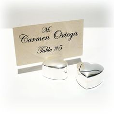 Silver Heart Placecard Holder (Set of 12)  Our silver plated heart place card holder is perfect to hold your guests names for the wedding reception and perfect for a picture after the wedding. Each measures 1 inches long, and 1 1/4 inch tall. Each placecard holder is velvet lined on the bottom. Place card slips in the groove at top. #weddingfavor #wedding #placecard #heart