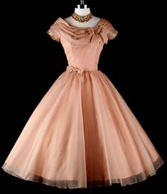 What a stunning peachy-pink 1950s dress!  It looks to me like a silk organza over taffeta, and the bows at waist and collar look really lovely.