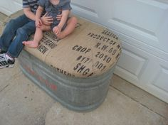 water trough turned storage bench covered in old coffee sacks. This would be cute on a porch or a kids room.