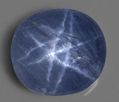 ♥ Rare Double-star Blue Sapphire.  Polished as an oval cabochon with a high dome, this sapphire of classic Sri Lankan cornflower blue, possesses a very unusual form of asterism: when the stone is illuminated with a single point light source, two superimposed six-rayed stars appear. The rays of one star are almost parallel to, and just to the side of, the other.