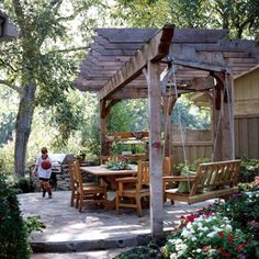 Backyard Dining Pergola. A cedar pergola overtop a flagstone patio makes an ideal backyard retreat. A grilling area allows food to be prepared tableside. And a porch swing, hanging on one end of the outdoor structure, provides an area to kick back and relax. The pergola-patio is edged with low-growing flowers. This is a lovely spot to enjoy! Landscaping Ideas, Backyard Landscaping, Porch Swings, Backyard Dine, Patio, Garden Structures, Pergola, Backyard Retreat, Backyards