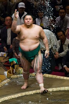 A sumo wrestler tosses salt to purify the ring at the Ryogoku stadium in Tokyo, Japan
