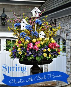 Spring urn planter flower arrangement with forsythia tulips daffodils and white bird houses. Serendipity Refined #Urn #floral #display