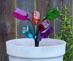 """Whimsical idea...having a """"baby"""" tree with tiny bottles, coming up by a larger one.  Like this idea"""
