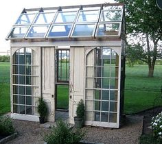 I love this greenhouse made from salvaged architectural parts. My geraniums would love living there for the winter.