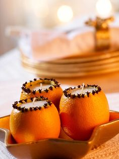 Hollowed out oranges, opening ringed with cloves, tea lights.
