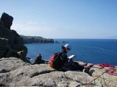 Climber reading guidebook near Land's End, Cornwall, England.