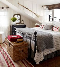 country coastal room with lovely iron bed, nautical red stripe decor, old oar, beachy linen / bedding and paired with a country feel - who doesn't love a bedroom by the Sea?