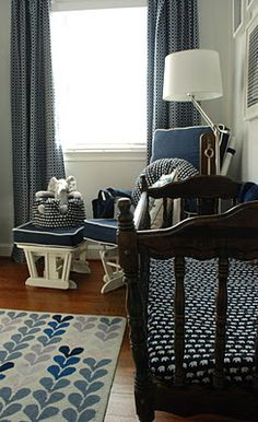 navy blue white elephant pattern baby boy nursery room with crib area and paper lanterns hanging over it