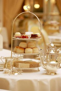 Afternoon tea with finger sandwiches and warm scones with clotted cream, macarons and eclairs