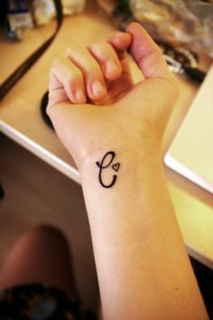 """C"" initial tattoo with small heart on wrist"
