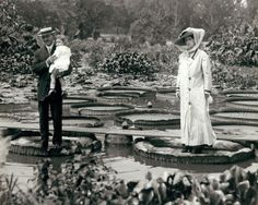 """Woman and man holding child standing on """"Victoria Regina"""" water lilies in Tower Grove Park. (1900)"""