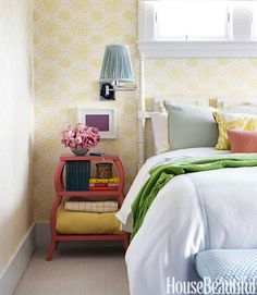 I like the little stand with flowers, books and extra bedding. Honeysuckle wallpaper behind the bed. Featured in House Beautiful.