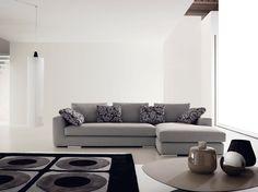 Composizione angolare moderna in tessuto grigio, completa di divano laterale sulla sinistra della lunghezza di 165 cm e di una panchetta laterale a destra della lunghezza di 100 cm.