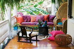 bohemian chic patio - bright colours, hide rug, fur & cane peacock chair