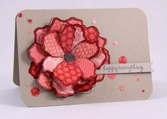 sweet handmade card ... huge layered flower ... each petal pieced from a different red print paper ... luv the addition of little circles punched from the scraps and placed randomly around the card ..