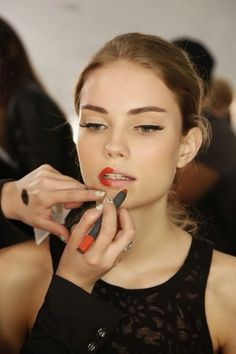 applying red lipstick before a fashion show