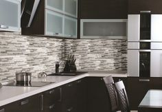 A kitchen backsplash using several shades of grey is trendy and compliments your cabinets.