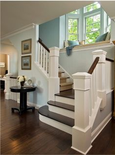 "I love all the natural light of the windows in the staircase. Wouldn't it be fun to also hang curtains in the window so someone could read there in a little ""secret"" hideout? I also love the black library table at the bottom of the stairs. Beautiful!"