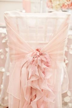 A frilly chair cover-- perfect for a blush and gold wedding.