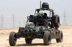 SEALs travel in a Desert Patrol Vehicle (DPV) in Kuwait, 2002. The DPV's weapons are covered to protect them from dust.