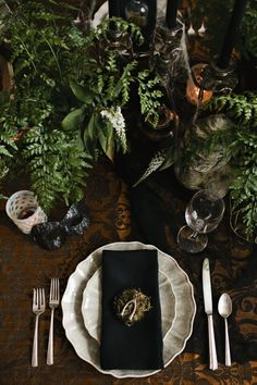 Halloween Midnight in the Garden place setting: black linen, bone-colored plates, surrounded by lush foliage, votives, garden statues, skulls and vintage candelabras