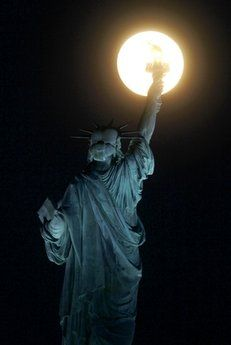 The moon rises near the Statue of Liberty as seen from Liberty State Park, Wednesday, June 15, 2011.