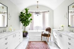 Serene bathroom with double vanities and arched nook for tub.