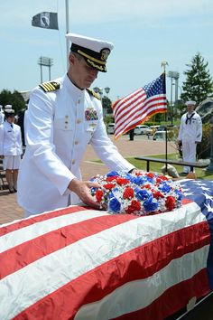 Capt. Steven Wieman, commanding officer of Naval Air Facility Atsugi, lays a wreath on a flag-draped coffin during a Memorial Day observance at Alliance Park.