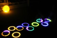 """Glowing Hopscotch! Just make hoops out of the glow in the dark bracelets or necklaces! Could use a standard glow in the dark stick to """"toss"""" or in our case, a glow in the dark bug of some sort! Lol Great activity for the kids when they aren't quite ready for bed but its gotten too dark for much else camping. -camping games for kids"""