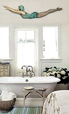 love this vintage style bathroom with just a hint of a nautical feel - white clawfoot bath, vintage art, coastal stripe and a rustic natural look with the baskets