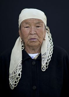 Old Woman Wearing A Headscarf At The Animal Market Of Kochkor, Kyrgyzstan by Eric Lafforgue.