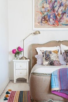 eclectic bedroom with modern art, an upholstered bed and a small white nightstand