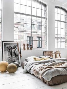 Loft, windows, bed, artwork, wood floor, white walls, photograph, decorative objects
