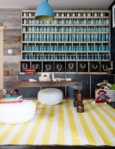 You'll Envy This Effortlessly Cool Family Home // blue bottle decor, white Moroccan poufs, yellow and white stripe rug, blue pendant light, wood walls