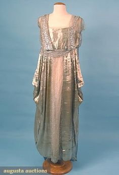 "SILVER LAME EVENING GOWN, 1915-1918  panels of silver lame & silver metallic mesh over silk chiffon, trimmed w/ 2.5"" wide silver lace, floating silver mesh & lace back panel"