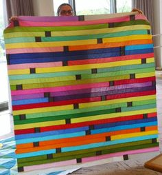Strip Race.  This quilt seems to be assembled with jelly roll strips. I like the idea of adding the small black squares. I had not seen that done before. Love that. That would make a great quilt for boys