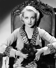 circa 1930: American film actress Carole Lombard (1908 - 1942) wearing a jacket with a leopard skin collar and cuffs, and holding a black cat on her lap.