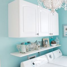 This is so bright and cheerful.... might make me look forward to laundry!! Love the cabinets to hide all the supplies too!